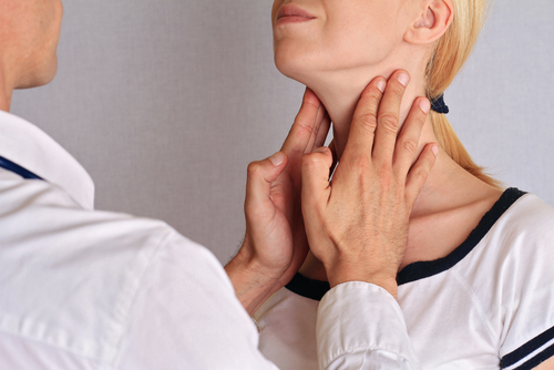 doctor feeling patients thyroid glands