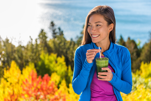 happy woman drinking green smoothie