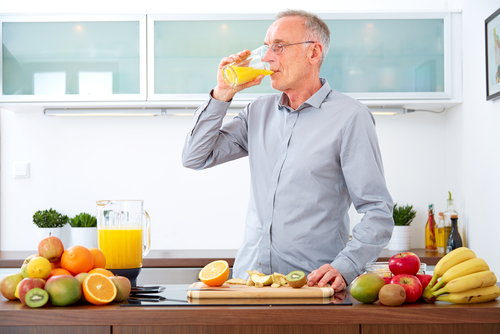 man drinking fresh squeezed orange juice