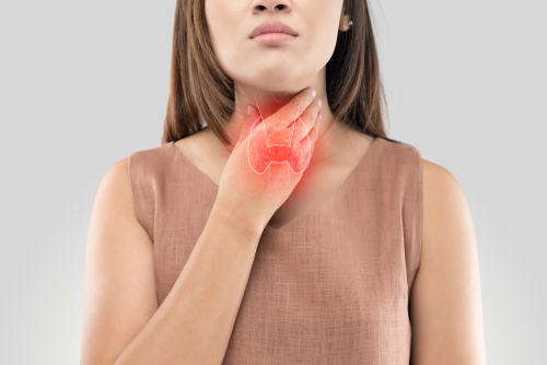 woman touching throat feeling thyroid glands
