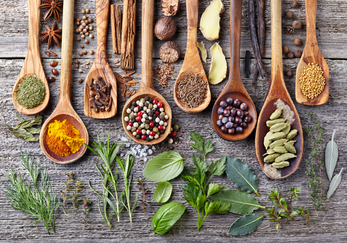 herbs spices on wooden spoons