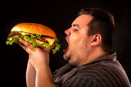 overweight person eating large hamburger