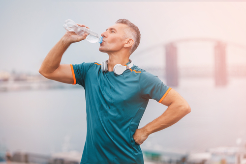 portrait athletic male drinking water