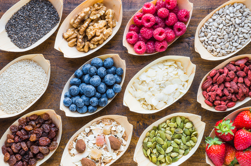 various superfoods on wood table top