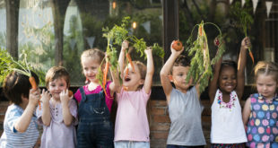 Group of children smiling and holding vegetables