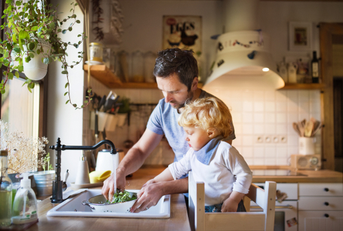 Young father with a toddler boy cooking