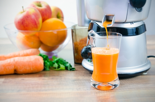 juicer pumping carrot juice into glass
