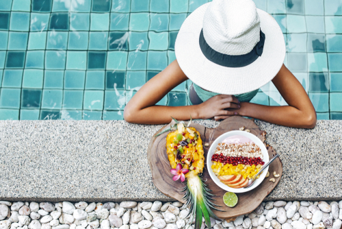 woman eating healthy food poolside