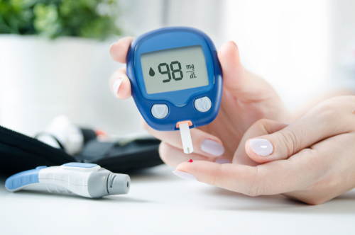 woman using glucometer at home