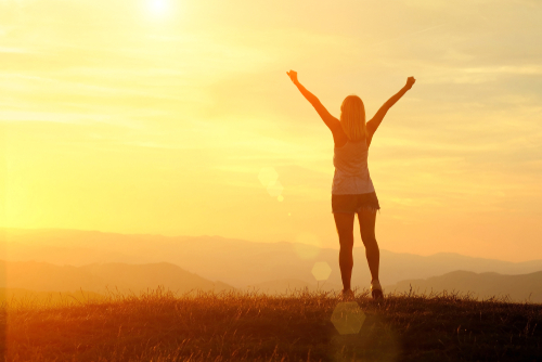 woman with arms outstretched against sunset