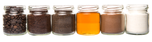 Coffee beans, coffee powder, creamer, cocoa powder, honey and processed tea leaves in a mason jars
