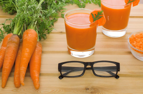 Two glasses of fresh carrot juice, bunch of carrot with green and black-rimmed spectacles on light wooden background
