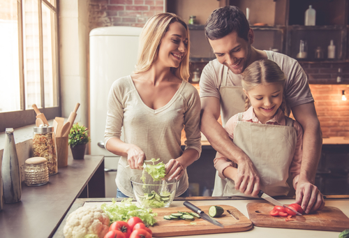 girl and her parents cutting vegetables