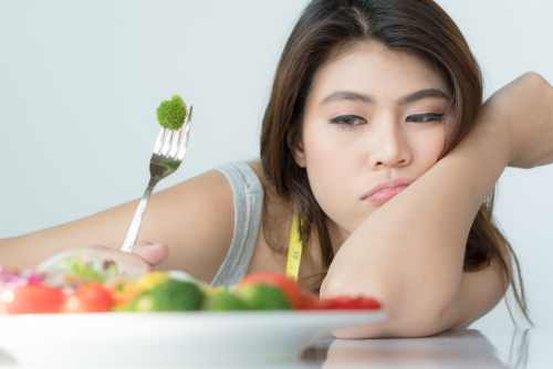 dieting woman looking at broccoli on fork