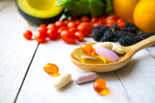 pill on wooden spoon with fruits