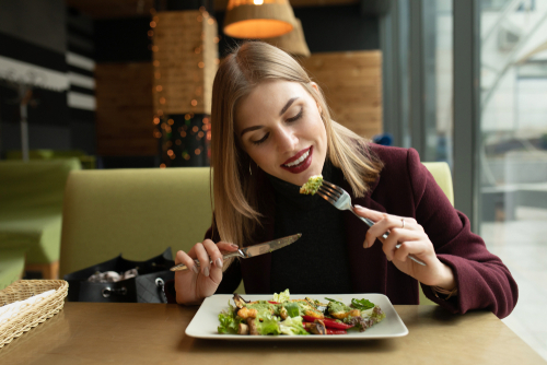 woman eating vegetable salad at restaurant