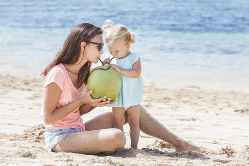 girl with mother drinking coconut water
